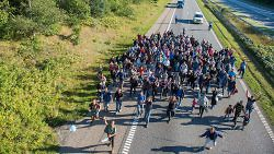 A large number of refugees walk north along the Danish E 45 Motorway near  Kliplev, Denmark, September 9, 2015. The refugees are trying to make it to Sweden on foot. (Benjamin Nolte/dpa/Corbis)