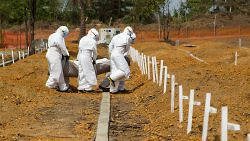 A burial team carries the body of a suspected Ebola victim to a grave in a new cemetery at Disco Hill, Liberia, January 26, 2015. (UN Photo/Martine Perret)