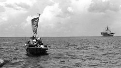 A thirty-five-foot fishing boat approaches a US navy ship 350 miles northeast of Cam Ranh Bay, Vietnam, after eight days at sea, May 15, 1984. US Department of the Navy.